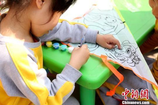 图为参与此次活动的儿童在现场画风筝。 张一辰 摄