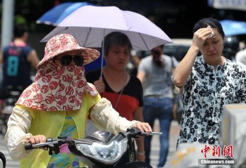 资料图:民众冒着高温出行。 张斌 摄