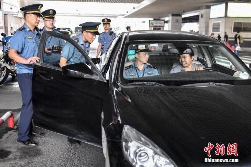 资料图:2018年5月16日,广州市交通委员会执法局执法人员在广州东站对网约车相关资质进行核查。中新社记者 陈骥�F 摄