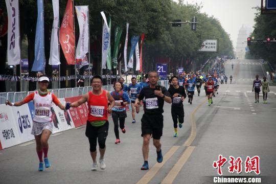 图为2018西安国际马拉松赛现场,参赛选手经过大雁塔。 张一辰 摄