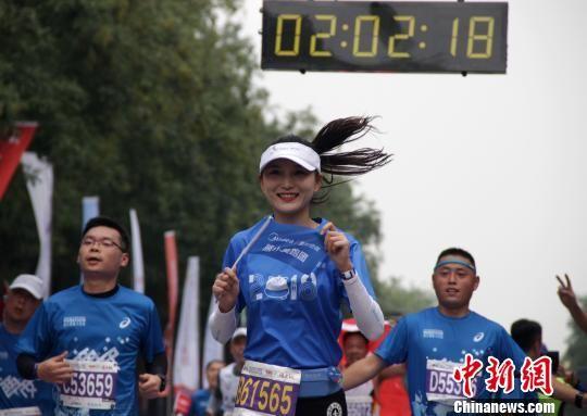 """图为2018西安国际马拉松赛现场,""""巾帼""""选手抢镜。 张一辰 摄"""