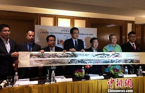 """8月12日,在吉隆坡举行的相关发布会上宣布""""2018国际郑和大会""""将于今年11月在马来西亚举行。图为承办方""""马六甲之窗""""执行长黄文庆(左二)向马来西亚民主行动党主席陈国伟(右三)赠送中国画家王新循画作《郑和下西洋》的复制品。中新社记者 陈悦 摄"""