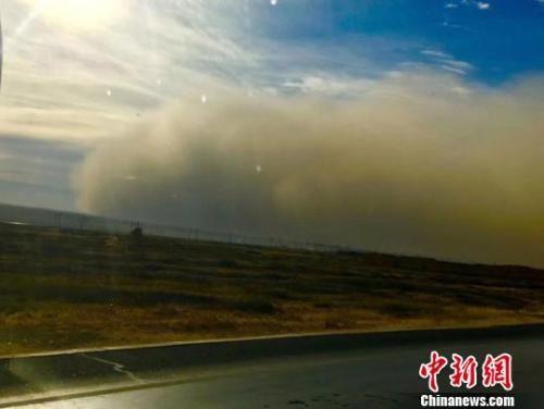 """11月25日下午,长约近千公里的甘肃河西走廊遭遇大风沙尘天气袭击,多地出现沙尘暴。图为张掖市境内现巨型""""沙墙""""向城市逼近。 杨红丽 摄"""