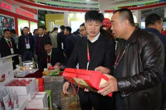 子长县副县长李茂胜(左一)在子长农副特色展示会上了解情况