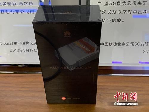资料图:部分友好测试用户拿到未开封的5G手机。 吴涛 摄