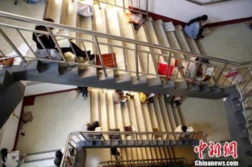 图为考研生坐在楼梯上专心背诵。 孙宏瑗 摄