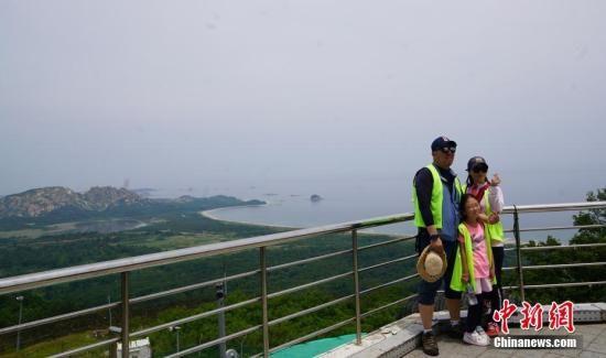 资料图:韩国民众在金刚山展望台合影,身后为朝鲜境内的金刚山。中新社记者 曾鼐 摄