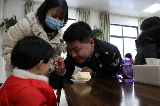 1月9日安康铁路公安处汉中站派出所食堂,民警与警嫂警宝一起分享节日蛋糕。