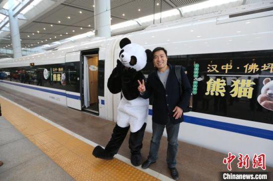 """资料图:西成高铁开通当日旅客与""""大熊猫""""合影。 张远 摄"""