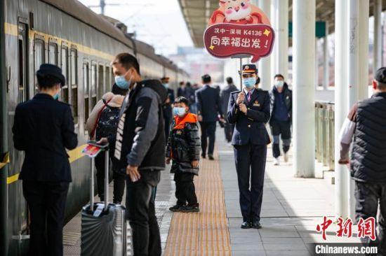 铁路工作人员手持指示牌引导旅客登上K4136次务工专列。 刘翔 摄