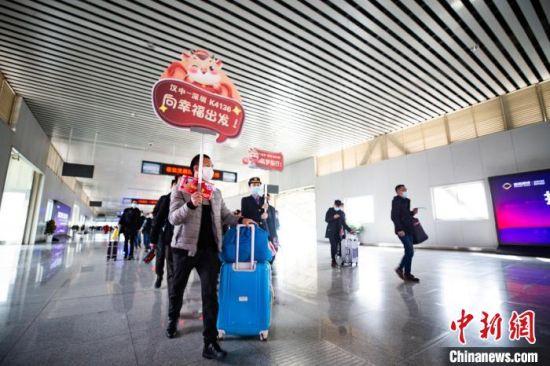 乘坐K4136次务工专列的旅客手拿铁路部门发放的爱心防疫包准备乘车。 刘翔 摄