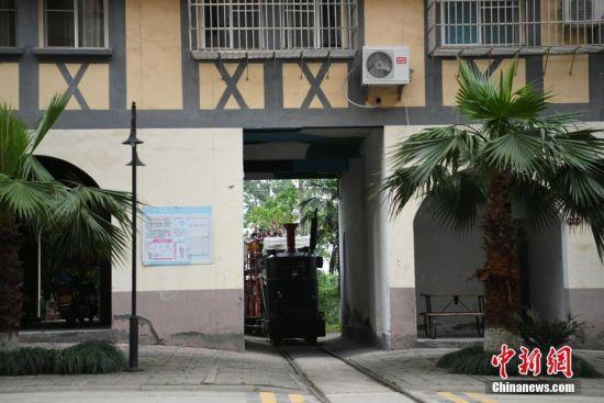 重庆一景区观光小火车从居民楼中穿过